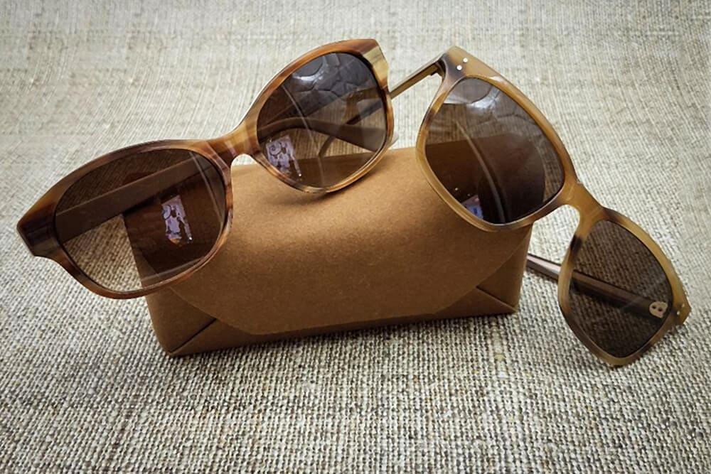 Zwei bräunliche Sonnenbrillen kombiniert mit dem farblich passenden Etui dazu