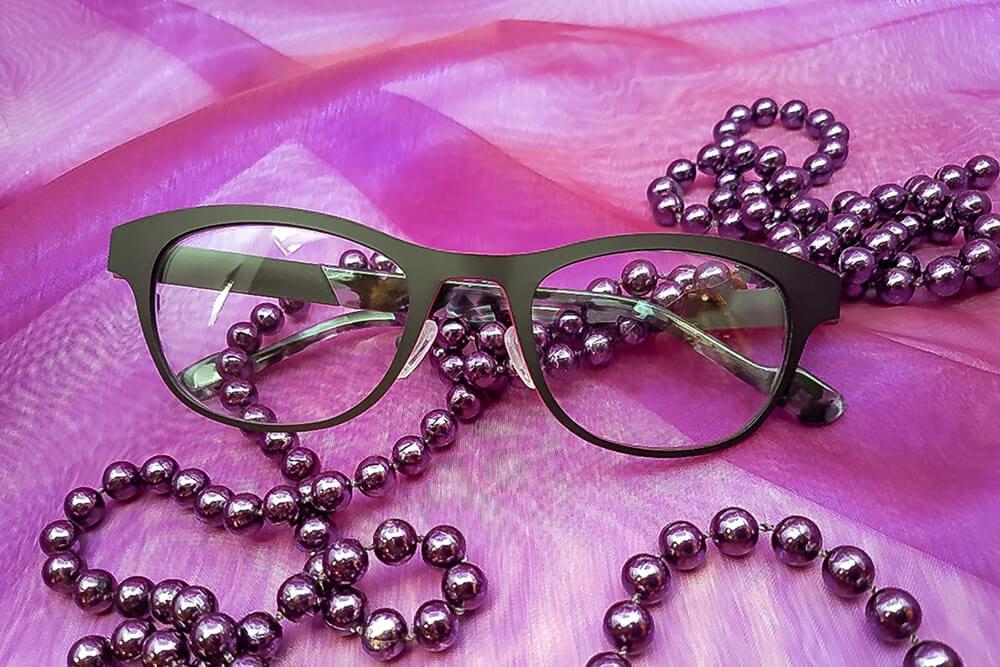 schwarze Brillenfassung auf feinem Stoff mit Perlenkette umrahmt