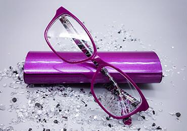 purplefarbene Brille mit passendem Etui umrahmt von Glitzersteinen
